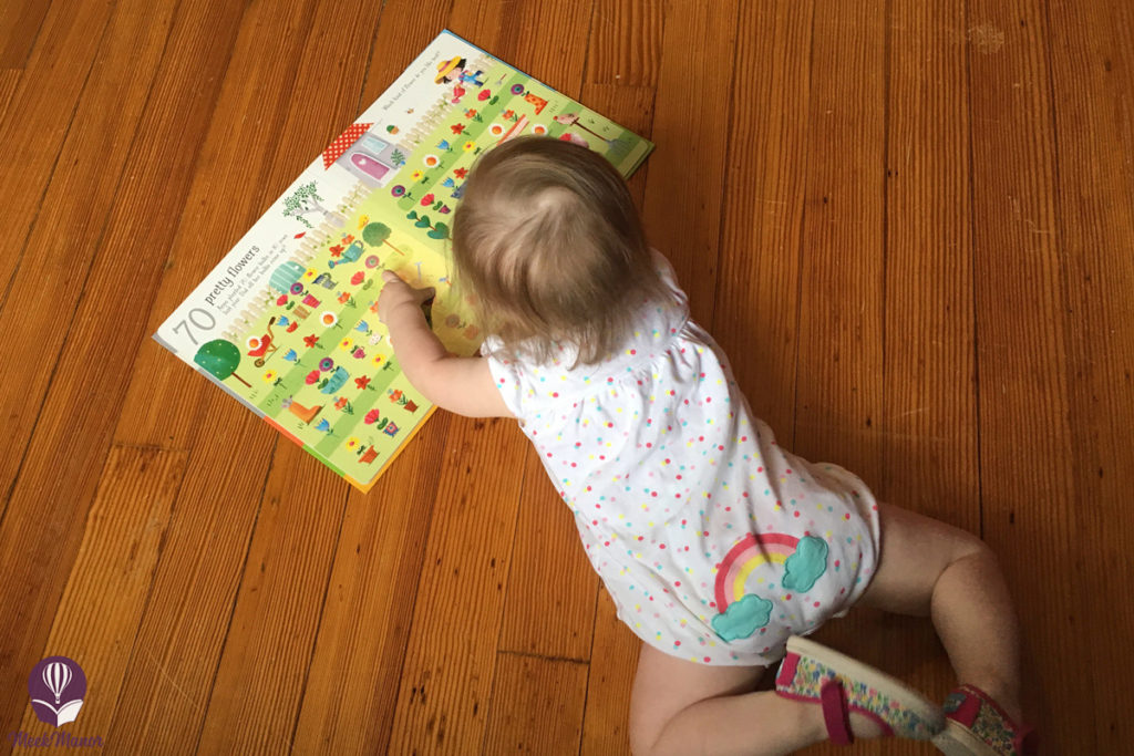 Toddler looking at book in Rainbow romper